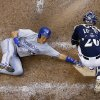 Photo - Milwaukee Brewers catcher Jonathan Lucroy can't handle the throw as Toronto Blue Jays' Munenori Kawasaki slides safely home during the sixth inning of a baseball game Wednesday, Aug. 20, 2014, in Milwaukee. Kawasaki scored from second on a hit by Jose Reyes. (AP Photo/Morry Gash)