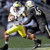 Michigan wide receiver Roy Roundtree, left, pushes off Purdue linebacker Will Lucas as he picks up 10 yards on a pass during the first half of an NCAA college football game in West Lafayette, Ind., Saturday, Oct. 6, 2012. (AP Photo/Michael Conroy)