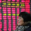 FILE - In this Friday Feb. 8, 2013, file photo, an investor looks at the stock price monitor at a private securities company in Shanghai, China. U.S. stocks are not alone in racing ahead this year. Many markets in Europe and Asia are trading at multi-year highs, too, in part because of Wall Street's rally. (AP Photo)