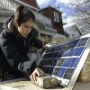 Arlae Castellanos sets up a solar charging station made by her high school students who are studying green energy, for hard-hit residents of the Rockaways who are still without power, Saturday, Nov. 3, 2012, on Beach 91st street in New York. More New Yorkers awoke Saturday to power being restored for the first time since Superstorm Sandy pummeled the region, but patience wore thin among those in the region who have been without power for most of the week. (AP Photo/Kathy Willens) ORG XMIT: NYKW113