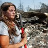 Her face dirtied from the mixture of sweat and ashes, Lori Turner holds the handle of a rake as she pauses from combing through the charred rubble of her mobile home on her property at 6000 NE 63 Wednesday after wildfires ravaged land and property that stretched from NE 50 on the south to Hefner Road on the north. Turner said she lost everything she had in this fire.