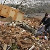 Hannah Rechel, from Dent, Ohio, helps recover personal items from debris after a tornado hit Friday in the village of Moscow, Ohio, Sunday, March 4, 2012. (AP Photo/David Kohl) ORG XMIT: OHDK107