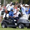 Photo - A spectator lifts up a rope as Tiger Woods, left, rides in a cart with his caddy Joe LaCava, center, after play was suspended due to approaching inclement weather during the first round of the Cadillac Championship golf tournament, Thursday, March 6, 2014, in Doral, Fla. (AP Photo/Lynne Sladky)