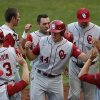 Oklahoma\'s Austin O\'Brien, center front, and Anthony Hermelyn, center rear, are greeted at the dugout after scoring against Oklahoma State during an NCAA college baseball game in Tulsa, Okla., on Saturday, May 17, 2014. (AP Photo/Tulsa World, Matt Barnard)
