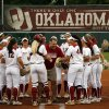 "Photo - Jim Routon, Moore tornado survivor and ""Big Dog"" in a photograph by Paul Hellstern that appeared following the deadly tornado, threw out the first pitch and celebrates with the team before the University of Oklahoma Sooner (OU) softball team plays Tennessee in the first game of the NCAA super regional at Marita Hynes Field on May 23, 2014 in Norman, Okla. Photo by Steve Sisney, The Oklahoman"