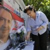 A supporter of Paraguayan presidential candidate, former Gen. Lino Oviedo, lights a candle at a makeshift memorial, backdropped by one of his campaign posters, at the entrance of the morgue where his remains were taken, in Asuncion, Paraguay, Monday, Feb. 4, 2013. The presidential hopeful died Saturday in a helicopter crash. Oviedo was returning with his bodyguard from a political rally in northern Paraguay Saturday night when his pilot encountered bad weather. All three were killed in the crash. (AP Photo/Jorge Saenz)