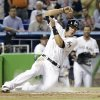 Photo - Miami Marlins' Derek Dietrich scores on a double hit by Casey McGehee in the first inning of a baseball game against the Atlanta Braves, Thursday, May 1, 2014, in Miami. (AP Photo/Lynne Sladky)