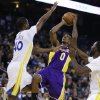 Photo - Los Angeles Lakers' Nick Young (0) shoots between Golden State Warriors' Harrison Barnes, left, and Draymond Green during the first half of an NBA basketball game Saturday, Dec. 21, 2013, in Oakland, Calif. (AP Photo/Ben Margot)
