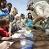 Photo -  Will Hagenbuck, an assistant naturalist at Martin Park Nature Center, shows children how to string beads for a water cycle bracelet. Photo by Paul Hellstern, The Oklahoman   PAUL HELLSTERN -