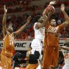 Oklahoma State\'s Stevie Clark (5) goes past Texas\' Martez Walker (24) and Cameron Ridley (55) during an NCAA college basketball game between the Oklahoma State Cowboys (OSU) and the University of Texas Longhorns at Gallagher-Iba Arena in Stillwater, Okla., Wednesday, Jan. 8, 2014. Oklahoma State won 87-74. Photo by Bryan Terry, The Oklahoman