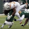 Photo - Texas running back Malcolm Brown (28) is stopped by Baylor's K.J. Morton (8) and Brody Trahan (15) during the first half of an NCAA college football game on Saturday, Dec. 7, 2013, in Waco, Texas. (AP Photo/LM Otero)