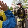 A firefighter gets a high-five on Gorilla Hill along Shartel Ave. near NW 40 St. during the Oklahoma City Memorial Marathon in Oklahoma City, Sunday, April 27, 2014. Photo by Nate Billings, The Oklahoman