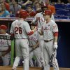 Photo - Philadelphia Phillies' Chase Utley (26) is congratulated by teammate Cody Asche (25) after Utley scored on a ground ball by Marlon Byrd against the Miami Marlins in the first  inning of a baseball game in Miami, Tuesday, May 20, 2014. (AP Photo/Alan Diaz)