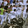 Revelers run with Valdefresno ranch fighting bulls on Estafeta street during the San Fermin fiestas, Tuesday, July 9, 2013, in Pamplona, Spain. Revelers from around the world come to participate in the street partying festival, which became world famous with the 1926 publication of Ernest Hemingway\'s novel