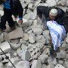 This citizen journalism image provided by Aleppo Media Center, AMC, which has been authenticated based on its contents and other AP reporting, shows a Syrian man carrying a child\'s body after a government airstrike hit the neighborhood of Eastern Ansari, in Aleppo, Syria, Sunday, Feb. 3, 2013. The Britain-based activist group Syrian Observatory for Human Rights, which opposes the regime, said government troops bombarded a building in Aleppo\'s rebel-held neighborhood of Eastern Ansari that killed over 10 people, including at least five children. (AP Photo/Aleppo Media Center AMC)