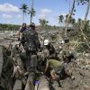 Soldiers retrieve the body of a victim in flash flood caused by Typhoon Bopha at New Bataan township, Compostela Valley in southern Philippines, Thursday Dec. 6, 2012. The powerful typhoon that washed away emergency shelters, a military camp and possibly entire families in the southern Philippines has killed hundreds of people with nearly 400 missing, authorities said Thursday. (AP Photo/Bullit Marquez)