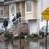 Rescue workers check a home for fuel leaks and other types of damage, Wednesday, Oct. 31, 2012, in the Staten Island borough of New York. Sandy, the storm that made landfall Monday, caused multiple fatalities, halted mass transit and cut power to more than 6 million homes and businesses. (AP Photo/ John Minchillo) ORG XMIT: NYJM113