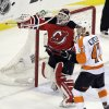 New Jersey Devils goalie Martin Brodeur, left, deflects the puck as Philadelphia Flyers\' Eric Wellwood looks on during the third period of Game 4 of a second-round NHL hockey Stanley Cup playoff series, Sunday, May 6, 2012 in Newark, N.J. The Devils won 4-2 and take a 3-1 lead in the series. (AP Photo/Julio Cortez)