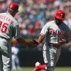 Photo - Philadelphia Phillies third base coach Pete Mackanin, left, congratulates Jimmy Rollins who circles the bases after hitting a solo home run against the Colorado Rockies in the first inning of a baseball game in Denver, Sunday, April 20, 2014. (AP Photo/David Zalubowski)