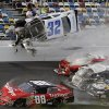 Photo - Kyle Larson (32) goes airborne and into the catch fence in a multi-car crash involving Dale Earnhardt Jr. (88), Parker Kligerman (77), Justin Allgaier (31) and Brian Scott (2) during the final lap of the NASCAR Nationwide Series auto race at Daytona International Speedway, Saturday, Feb. 23, 2013, in Daytona Beach, Fla. (AP Photo/John Raoux)
