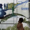 Photo - A woman passes by Samsung Electronics Co.'s showroom in Seoul, South Korea, Tuesday, July 8, 2014. Samsung Electronics Co. said operating profit declined to a two-year low in the second quarter, hit by the strong local currency and slowing demand for smartphones in China.(AP Photo/Ahn Young-joon)