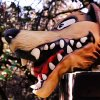 A mask representing The Big Bad Wolf protrudes from the top of a chimney on a
