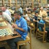 Edmond Rotary Club members play chess with the award-winning team at Ida Freeman Elementary School. Among participants are Edmond Mayor Charles Lamb, right of center (wearing yellow shirt), who ponders his next move. [Photo provided]