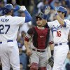Photo - Los Angeles Dodgers' Andre Ethier, right, and Matt Kemp, left, celebrate a three-run home run hit by Ethier in front of Arizona Diamondbacks catcher Miguel Montero during the fourth inning of a baseball game on Saturday, April 19, 2014, in Los Angeles. (AP Photo/Jae C. Hong)
