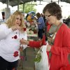 Lorie Mumby, left, designer for Heavenly Hummers Hummingbird Feeders, tells Chris Mathews how they can be attached at the Farmers Market in Edmond Saturday, May 9, 2009. Photo by Doug Hoke, The Oklahoman