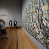 """Photo - Members of the media preview Jackson Pollock's """"Mural,"""" 1943, at the J. Paul Getty Museum in Los Angeles on Monday, March 10, 2014. The oil-on-canvas work, measuring more than 8 feet high and nearly 20 feet long, has been under wraps at the J. Paul Getty Museum for more than a year undergoing extensive restoration. The painting, owned by the University of Iowa, will be on display at The J. Paul Getty Museum for three months, from March 11 to June 1, 2014 at the Getty Center. (AP Photo/Nick Ut )"""
