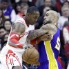 Photo - Houston Rockets' Dwight Howard, left, is fouled by Los Angeles Lakers' Robert Sacre in the first half of an NBA basketball game on Wednesday, Jan. 8, 2014, in Houston. (AP Photo/Pat Sullivan)