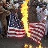 Photo - Supporter of the Pakistani religious party Jamaat-u-Dawa burn a representation of a U.S. flag during a rally to condemn U.S. drone attacks in Pakistan, in Karachi, Pakistan, Friday, Nov. 1, 2013. (AP Photo/Shakil Adil)