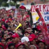 Supporters of Venezuela\'s President Hugo Chavez, one holding up a mask representing Chavez, attend a campaign rally in Valencia, Venezuela, Wednesday, Oct. 3, 2012. Chavez is running for re-election against opposition candidate Henrique Capriles in presidential elections on Oct . 7. (AP Photo/Rodrigo Abd)