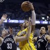 Photo - Indiana Pacers forward Paul George, center, grabs a rebound between Brooklyn Nets forward Mirza Teletovic, left, and guard Shaun Livingston in the second half of an NBA basketball game in Indianapolis, Saturday, Feb. 1, 2014. The Pacers defeated the Nets 97-96. (AP Photo/Michael Conroy)