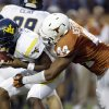 West Virginia quarterback Geno Smith, left, is sacked by Texas defender Jackson Jeffcoat (44) during the second quarter of an NCAA college football game on Saturday, Oct. 6, 2012, in Austin, Texas. (AP Photo/Eric Gay) ORG XMIT: TXEG113