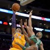 Photo - Los Angeles Lakers guard Kobe Bryant (24) shoots over Boston Celtics forward Chris Wilcox, right, and guard Jason Terry (4) during the first half of their NBA basketball game, Wednesday, Feb. 20, 2013, in Los Angeles. (AP Photo/Mark J. Terrill)