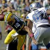 Photo - Green Bay Packers quarterback Aaron Rodgers tries to avoid Detroit Lions' Ndamukong Suh (90) during the first half of an NFL football game Sunday, Oct. 6, 2013, in Green Bay, Wis. (AP Photo/Jeffrey Phelps)
