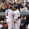 Minnesota Twins\' Jamey Carroll, left, is greeted by teammate Ben Revere after scoring on a single by Pedro Florimon in the seventh inning of a baseball game Sunday, Sept. 30, 2012 in Minneapolis. At right is manager Ron Gardenhire. The Tigers won 2-1. (AP Photo/Jim Mone)