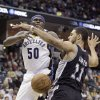 Photo - Memphis Grizzlies' Zach Randolph (50) looses the ball in front of San Antonio Spurs' Jeff Ayres (11) in the first half of an NBA basketball game in Memphis, Tenn., Tuesday, Jan. 7, 2014. (AP Photo/Danny Johnston)