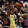 Photo - Indiana Pacers forward Paul George (24) passes the basketball between Chicago Bulls guard Jimmy Butler (21) and forward Taj Gibson during the first half of an NBA basketball game in Indianapolis, Friday, March 21, 2014. (AP Photo/R Brent Smith)