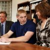 Photo - NATIONAL SIGNING DAY: Norman North football player Brenden Brown, surrounded by parents Dale and Christine, , signs a letter of intent to play college football n the high school's library on Wednesday, Feb 3, 2010, in Norman, Okla.  Photo by Steve Sisney, The Oklahoman ORG XMIT: KOD