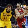 Photo - Chicago Bulls' Joakim Noah, right, drives the lane on Cleveland Cavaliers' Anderson Varejao (17), of Brazil, in the second quarter of an NBA basketball game Wednesday, Jan. 22, 2014, in Cleveland. (AP Photo/Mark Duncan)