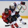 Photo - Meghan Duggan of the United States and Brianne Jenner of Canada races after the puck during the second period of the 2014 Winter Olympics women's ice hockey game at Shayba Arena, Wednesday, Feb. 12, 2014, in Sochi, Russia. (AP Photo/Petr David Josek)