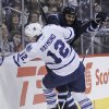 Photo - Winnipeg Jets' Dustin Byfuglien (33) checks Toronto Maple Leafs' Mason Raymond (12) during the second period of an NHL hockey game Saturday, Jan. 25, 2014, in Winnipeg, Manitoba. (AP Photo/The Canadian Press, Jason Woods)