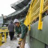 Photo - James Diedrick helps clear ice and snow from the seats at Lambeau Field on Friday, Jan. 3, 2014, in Green Bay, Wis., in preparation for Sunday's NFL football wild-card playoff game between the Green Bay Packers and San Francisco 49ers. (AP Photo/Mike Roemer)