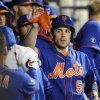 Photo - New York Mets' David Wright high-fives with teammates in the dugout after scoring on a double hit by Daniel Murphy against the  Miami Marlins in the third inning of a baseball game at Citi Field on Friday, April 25, 2014, in New York. (AP Photo/Kathy Kmonicek)