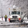 Photo - A utility truck is parked on a street to help restore power to a neighborhood in North Lansing, Mich. on Sunday, Dec. 22, 2013. Winter arrived in Michigan with an icy blast, sending freezing rain across a wide section of the Lower Peninsula and knocking out electrical service to at last 294,000 homes and businesses. The state's largest utilities say it will be days before most of those blacked out get their power back because of the difficulty of working around ice-broken lines.  (AP Photo/Lansing State Journal, Robert Killips)