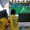 Photo - A couple of young soccer fans, watch on a giant screen television  Brazil play Cameroon in the soccer World Cup match, in Manaus, Brazil, Monday, June 23, 2014. Brazil's Neymar scored twice in the first half to lead Brazil to a 4-1 win over Cameroon on Monday, helping the hosts secure a spot in the second round of the soccer World Cup. (AP Photo/Martin Mejia)