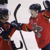 Photo - Florida Panthers' Scottie Upshall, right, celebrates with teammate Brian Campbell (51) after Upshall scored a goal during the third period of an NHL hockey game against the New Jersey Devils, Friday, March 14, 2014, in Sunrise, Fla. The Panthers won 5-3. (AP Photo/Luis M. Alvarez)