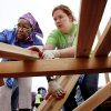 Marie Hopkins, left, and Tara Simmons place wooden planks on top of boards as they make a platform on the playground. Organizers said about 140 volunteers from Partners in Public Health, Blue Cross and Blue Shield of Oklahoma, organizers from KaBOOM! and residents of the Oklahoma City community will provided the labor on Saturday, June 8, 2013, to build a new playground at the Northeast Regional Health and Wellness Center on NE 63 Street, east of MLK Blvd. The new playground\'s design is based on drawings created by children who participated in a Design Day event in April. Photo by Jim Beckel, The Oklahoman.